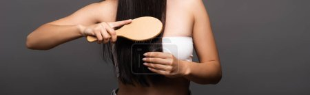 cropped view of brunette woman brushing shiny hair isolated on black, panoramic shot