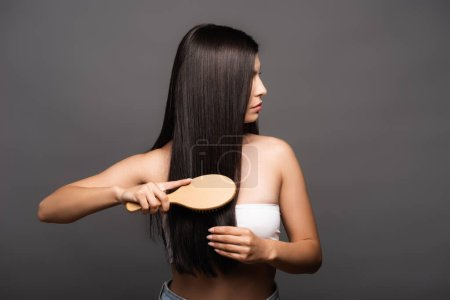 Photo pour Cropped view of brunette woman brushing shiny hair isolated on black - image libre de droit