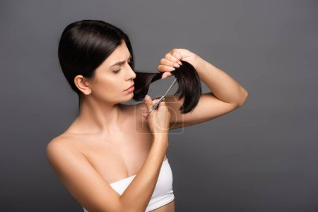 brunette woman cutting hair isolated on black