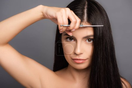 Naked brunette woman cutting hair isolated on blac...