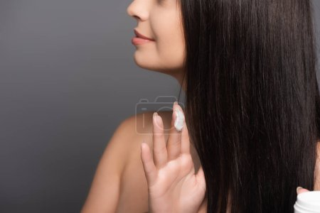 cropped view of brunette woman showing hair mask on fingers isolated on black