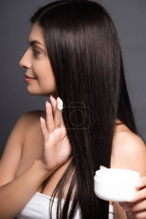 selective focus of brunette long haired woman holding hair mask isolated on black