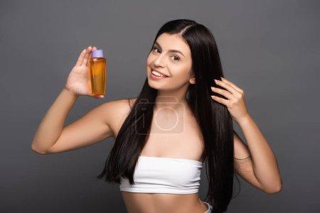 brünette Frau mit Haaröl in Flasche isoliert auf schwarz