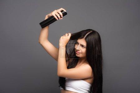 Photo pour Brunette femme aux cheveux longs appliquant spray capillaire isolé sur noir - image libre de droit