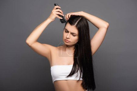 sad brunette long haired woman shaving head with electric razor isolated on black