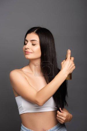Photo pour Brunette femme pulvérisation huile sur cheveux isolés sur noir - image libre de droit