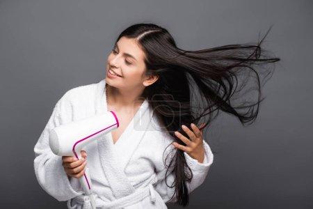 Photo pour Brunette femme aux cheveux longs en peignoir en utilisant sèche-cheveux isolé sur noir - image libre de droit