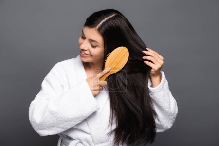 Photo for Brunette woman in bathrobe brushing hair and smiling isolated on black - Royalty Free Image