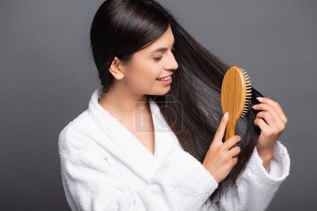 Photo pour Brunette femme en peignoir brossant les cheveux et souriant isolé sur noir - image libre de droit