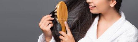 Photo pour Brunette femme en peignoir brossant les cheveux et souriant isolé sur noir, panoramique shot - image libre de droit