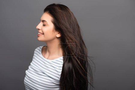 Photo pour Vue latérale du vent soufflant à travers les cheveux de la femme brune aux yeux fermés isolé sur noir - image libre de droit
