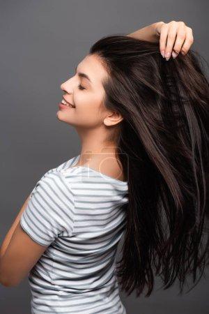Photo pour Vue latérale de la femme brune aux yeux fermés cheveux souriants et touchants isolés sur noir - image libre de droit