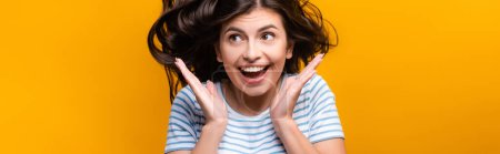 Photo for Brunette long haired woman with curls jumping and smiling isolated on yellow, panoramic shot - Royalty Free Image