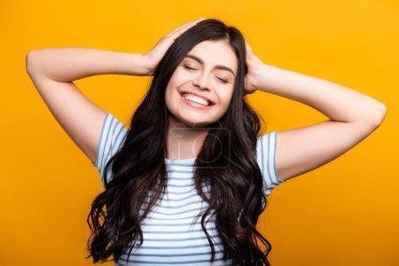 brunette femme aux cheveux longs avec des boucles touchant la tête et souriant isolé sur jaune