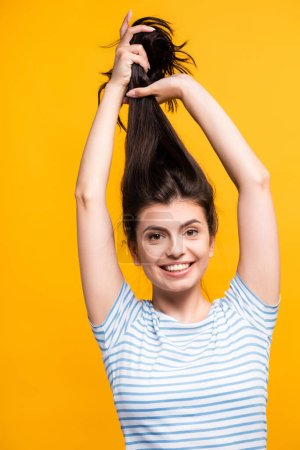 Photo for Brunette woman holding hair above head and smiling isolated on yellow - Royalty Free Image