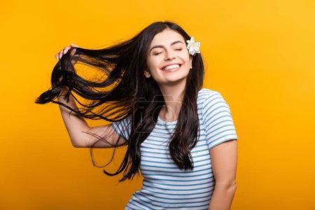 brünette junge Frau mit Blumen im Haar und geschlossenen Augen, die isoliert auf gelb lächelt