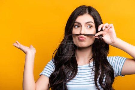 Photo pour Femme brune avec des boucles faisant fausse moustache à partir de cheveux isolés sur jaune - image libre de droit