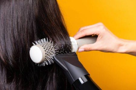 Photo pour Vue recadrée du coiffeur en utilisant sèche-cheveux et brosse isolée sur jaune - image libre de droit