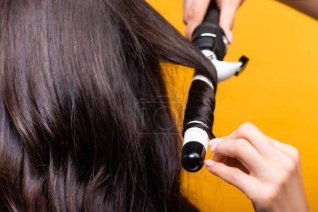 Photo pour Vue recadrée du coiffeur à l'aide de fer à friser isolé sur jaune - image libre de droit
