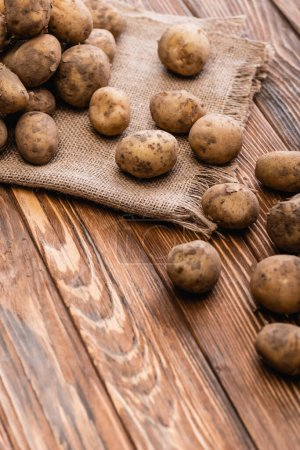 dirty potatoes and burlap on wooden table