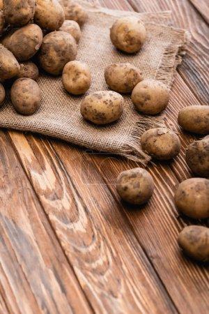 Photo pour Pommes de terre sales et toile de jute sur table en bois - image libre de droit