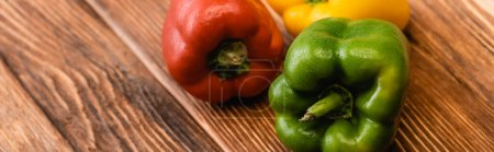 colorful ripe bell peppers on wooden table, panoramic shot