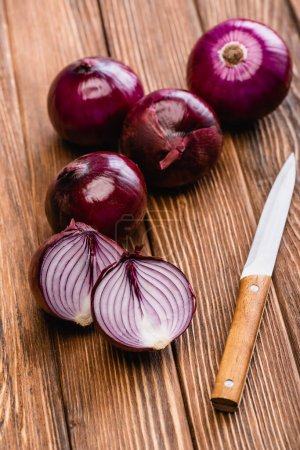 Photo for Cut and whole red onion near knife on wooden table - Royalty Free Image