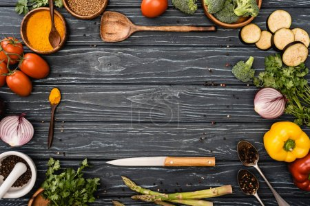 Photo for Top view of fresh colorful vegetables, spices near knife and spatula on wooden surface - Royalty Free Image