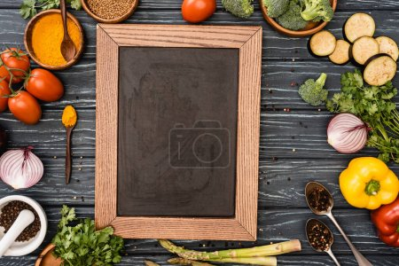 top view of fresh colorful vegetables and empty chalkboard on wooden table