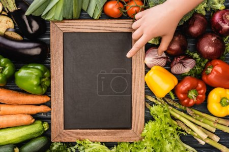 cropped view of person pointing at empty chalkboard near fresh colorful vegetables