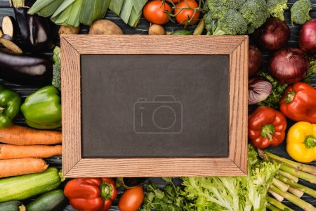 top view of fresh colorful vegetables around empty chalkboard