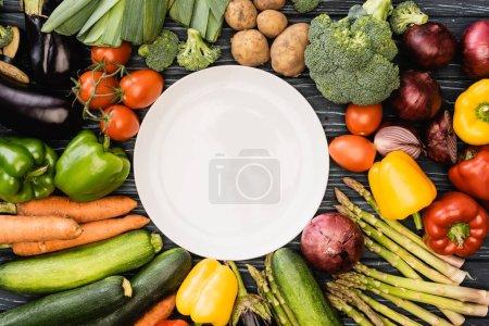 Photo pour Vue de dessus des légumes colorés frais autour de la plaque vide - image libre de droit