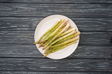Photo for Top view of fresh asparagus on plate on wooden surface - Royalty Free Image