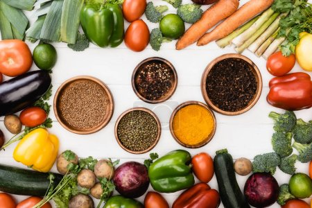 Photo pour Vue de dessus des légumes frais mûrs et des fruits autour des bols avec des épices sur fond blanc en bois - image libre de droit