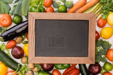 top view of fresh ripe vegetables and fruits near empty chalkboard