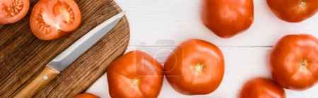 Photo for Top view of ripe tomatoes on chopping board with knife on white wooden table, panoramic shot - Royalty Free Image
