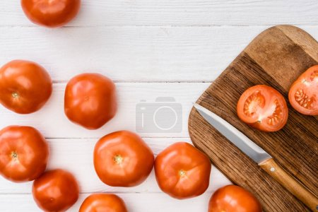 Photo for Top view of ripe tomatoes on chopping board with knife on white wooden table - Royalty Free Image