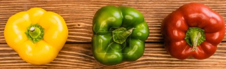 Photo for Top view of colorful ripe bell peppers on wooden table, panoramic shot - Royalty Free Image