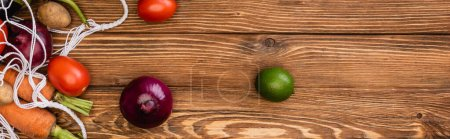 Photo for Top view of fresh ripe vegetables scattered from string bag on wooden table, panoramic shot - Royalty Free Image