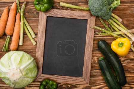 top view of fresh ripe vegetables and empty chalkboard on wooden background