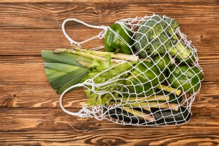 top view of fresh green ripe vegetables in string bag on wooden table