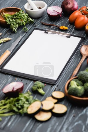 selective focus of blank clipboard near spices and vegetables on wooden surface