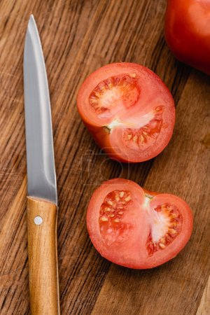 Photo for Top view of ripe tomato halves on wooden chopping board with knife - Royalty Free Image