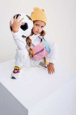 Photo pour Fille blonde en vêtements de sport posant avec ballon de football sur cube isolé sur blanc - image libre de droit