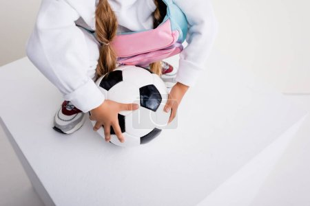 cropped view of girl in sportswear posing with soccer ball on cube