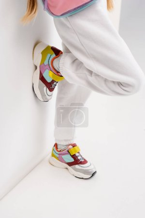 Photo for Blonde girl in sportswear posing near wall on white background - Royalty Free Image