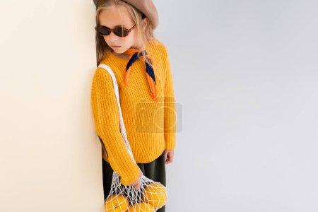 Photo pour Fille blonde à la mode en tenue d'automne et lunettes de soleil posant avec des pamplemousses dans un sac à ficelle sur fond beige et blanc - image libre de droit