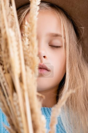 Photo pour Selective focus of fashionable blonde girl in hat and blue sweater in wheat spikes with closed eyes - image libre de droit