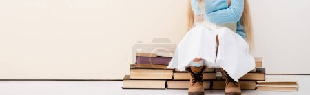 Photo for Cropped view of fashionable blonde girl in brown boots, white skirt and blue sweater sitting with book near beige wall, panoramic shot - Royalty Free Image