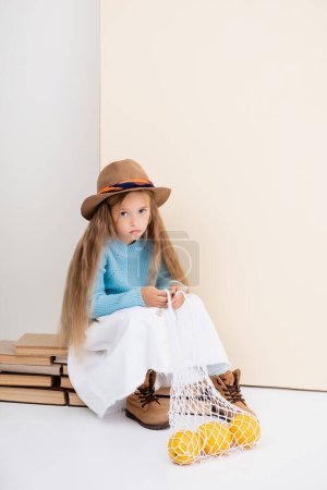 Photo for Fashionable blonde girl in brown hat and boots, white skirt and blue sweater sitting on vintage books with grapefruits in string bag - Royalty Free Image